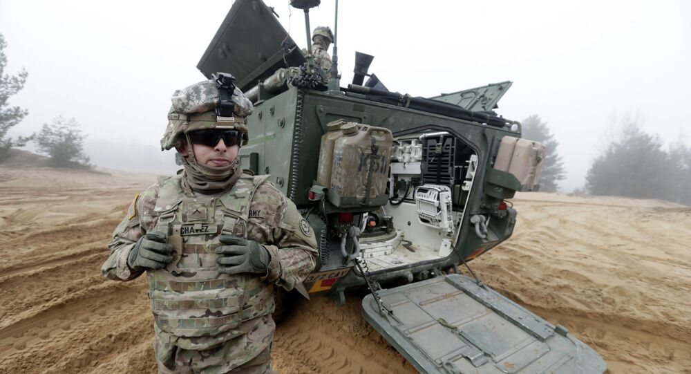 Soldiers of the U.S. Army's 2nd Cavalry Regiment, deployed in Latvia as part of the US Operation Atlantic Resolve, are pictured near their armored vehicle named Stryker during a joint military exercise in Adazi, Latvia