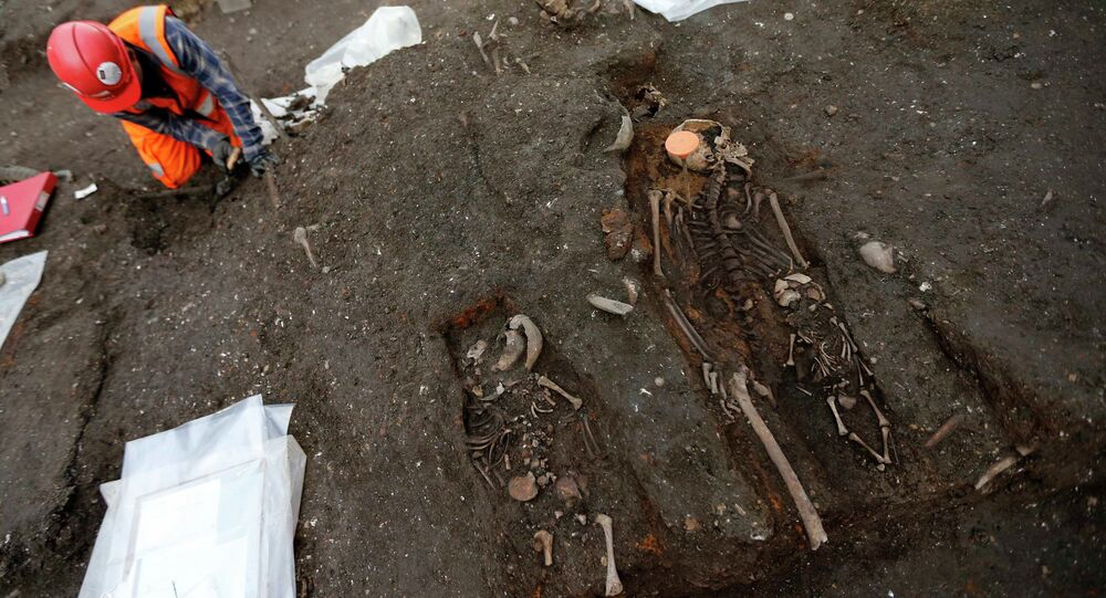 An archaeologist works near skeletons of a mother and two children found in the Bedlam burial ground on the future site of a Crossrail ticket hall next to Liverpool Street Station in London