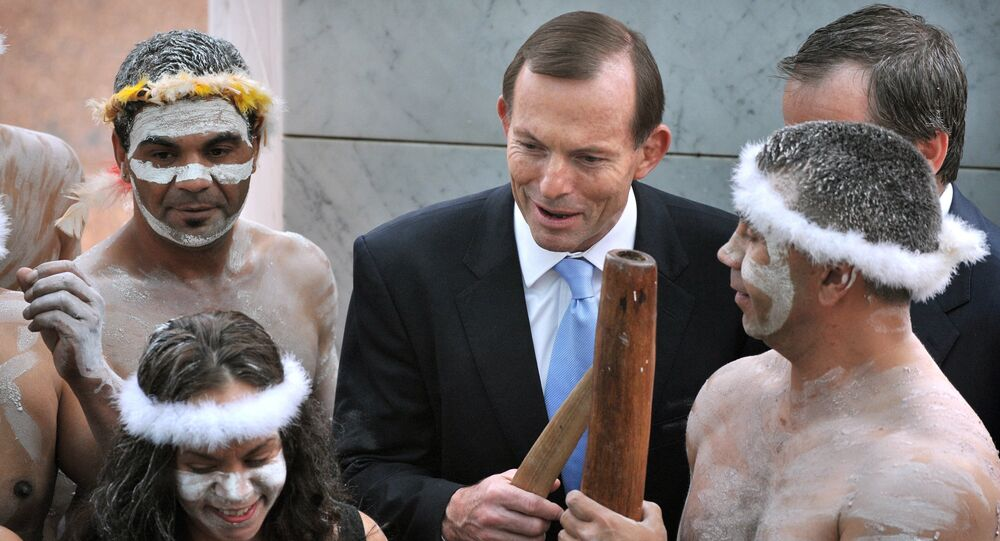 A file photo taken on November 12, 2013, shows Australian Prime Minister Tony Abbott holding his fighting boomerang while talking to an Aboriginal performer at the opening of the 44th Parliament in Canberra. Abbott faced a wave of criticism on March 11, 2015