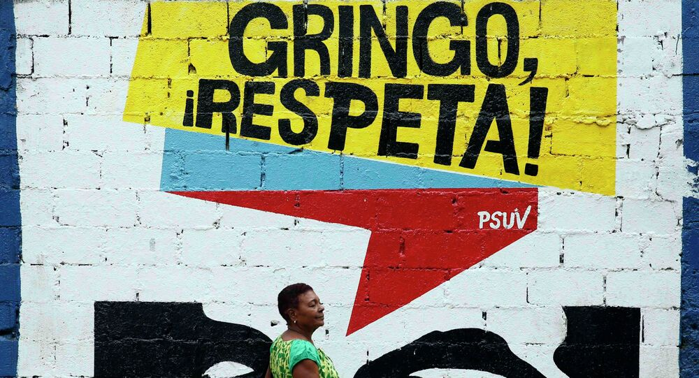 A woman walks past graffiti which reads Gringo, respect us! in Caracas March 10, 2015. President Nicolas Maduro was seeking special decree powers from Venezuela's parliament on Tuesday in response to new U.S. sanctions, drawing opposition protests of a power-grab