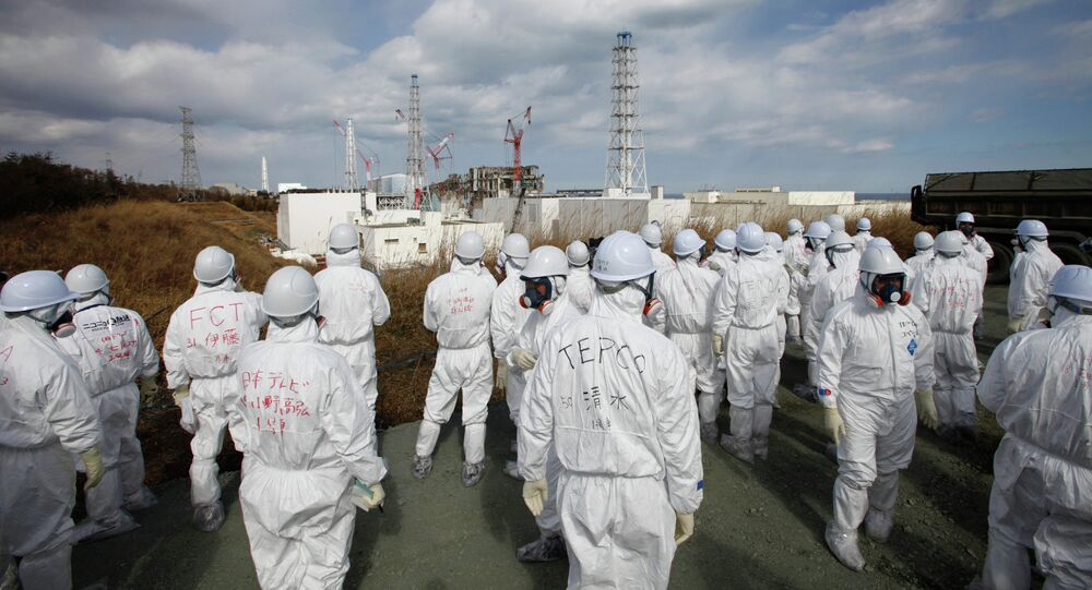 Members of the media wearing protective suits and masks report as they are escorted by TEPCO employees at Tokyo Electric Power Co. (TEPCO)'s tsunami-crippled Fukushima Daiichi nuclear power plant in Okuma, Fukushima prefecture on February 20, 2012