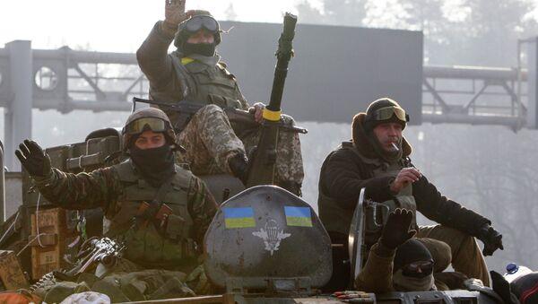 Ukrainian servicemen ride atop an armoured personnel carrier (APC), as they return from the frontline in eastern Ukraine, in Kiev March 11, 2015 - Sputnik International