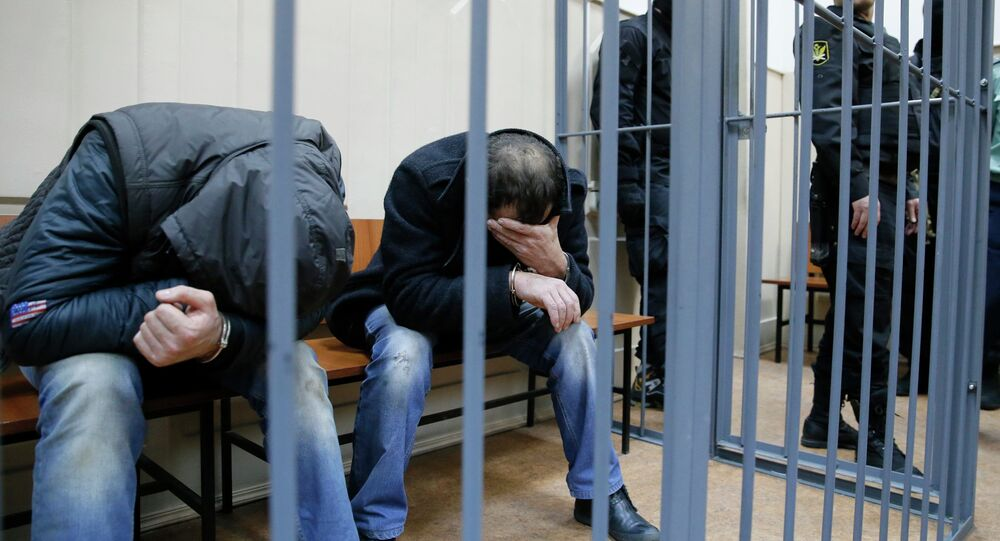 Shagid Gubashev (L) and Ramzan Bakhayev, detained over the killing of Russian opposition figure Boris Nemtsov, hide their faces inside a defendants' cage at a court building in Moscow March 8, 2015