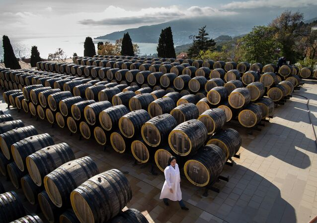 In this photo taken on Tuesday, Oct. 28, 2014, a woman walks by barrels of wine in the state-owned Massandra winery in Yalta, Crimea
