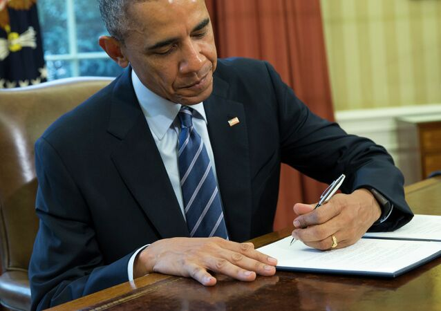 President Barack Obama signs a presidential memorandum aiming to clamp down on the private companies that service federal student debt