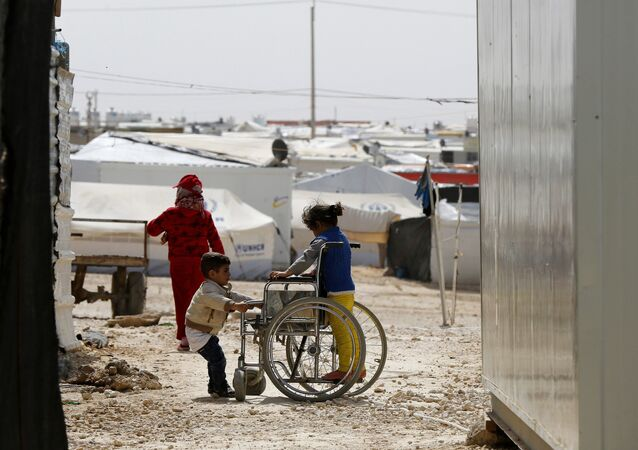 Syrian refugee children play with a wheelchair at the Al Zaatari refugee camp in the Jordanian city of Mafraq, near the border with Syria March 11, 2015