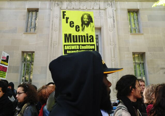 Protestors stand before an image of Mumia Abu-Jamal outside the US Department of Justice on April 24, 2012 in Washington