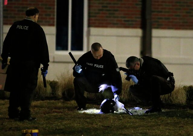 Police shine a light on and photograph a helmet as they investigate the scene where two police officers were shot outside the Ferguson Police Department Thursday, March 12, 2015, in Ferguson, Mo
