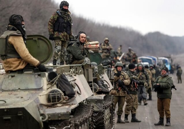 Members of the Ukrainian armed forces and armoured personnel carriers are seen preparing to move as they pull back from Debaltseve region, near Artemivsk February 26, 2015
