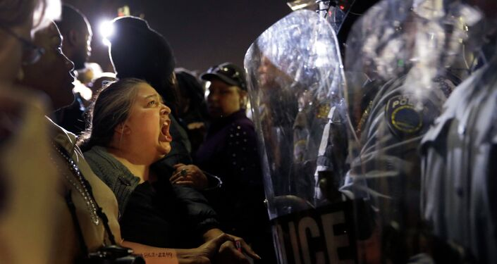 A protester yells at police outside the Ferguson Police Department