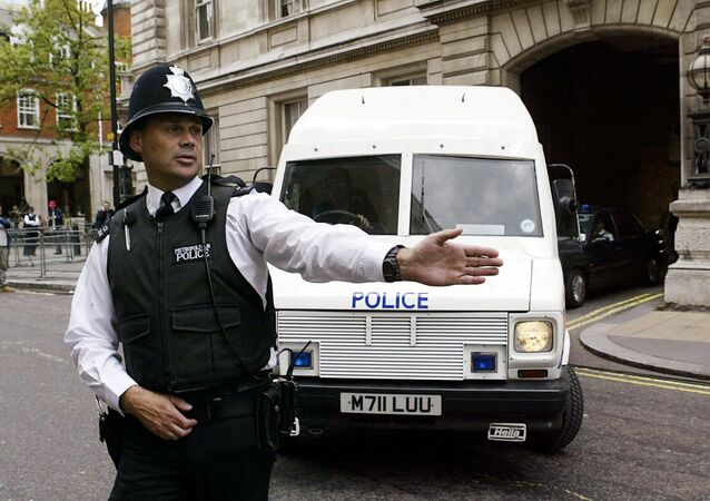 A policeman stops traffic as an armoured policevan leaves Bow street magistrates court in central London