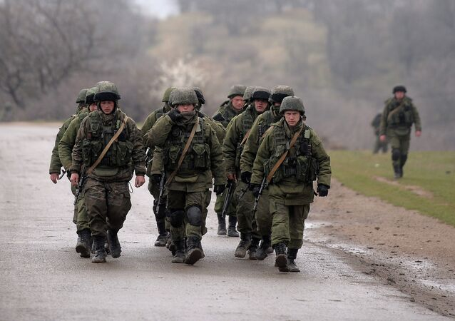Russian soldiers patrol the area surrounding the Ukrainian military unit in Perevalnoye, outside Simferopol, on March 20, 2014