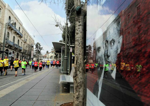 Athletes, participating in the fifth international Jerusalem Marathon, run near a poster of Israeli Prime Minister Benjamin Netanyahu (L) and Naftali Bennett, head of far-right Jewish Home party, four days ahead of parliamentary elections, March 13, 2015