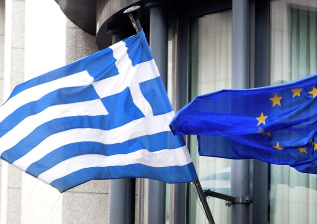 The Greek, left, and EU flag flap in the wind