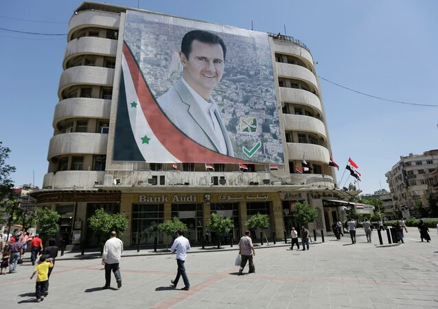 Syrians walk past a giant campaign billboard of Syrian President Bashar al-Assad on June 1, 2014 in the capital Damascus