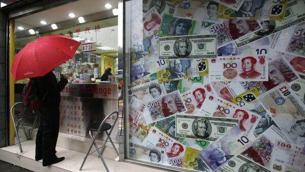 A man stands beside a collage of copies of Chinese RMB, U.S. dollar and other foreign bills at a money exchange store in Hong Kong Thursday, April 15, 2010 - Sputnik International