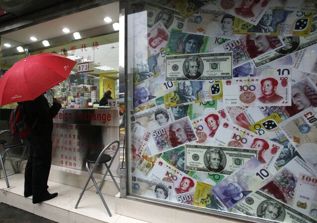A man stands beside a collage of copies of Chinese RMB, U.S. dollar and other foreign bills
