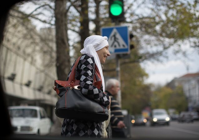 In this photo taken on Thursday, Oct. 23, 2014, a woman in traditional Tatar women's headscarf wait to cross the road in Simferopol, Crimea