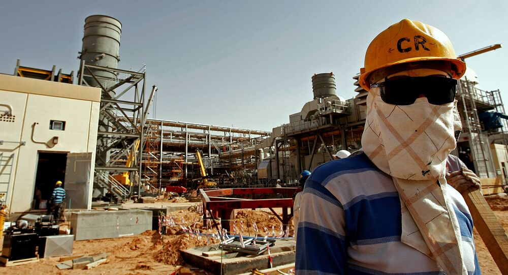 An Asian worker covers his face to protect it from the dust and the blazing sun at the site of Saudi Aramco's (the national oil company) Al-Khurais central oil processing facility under construction in the Saudi Arabian desert, 160 kms east of the capital Riyadh, on June 23, 2008