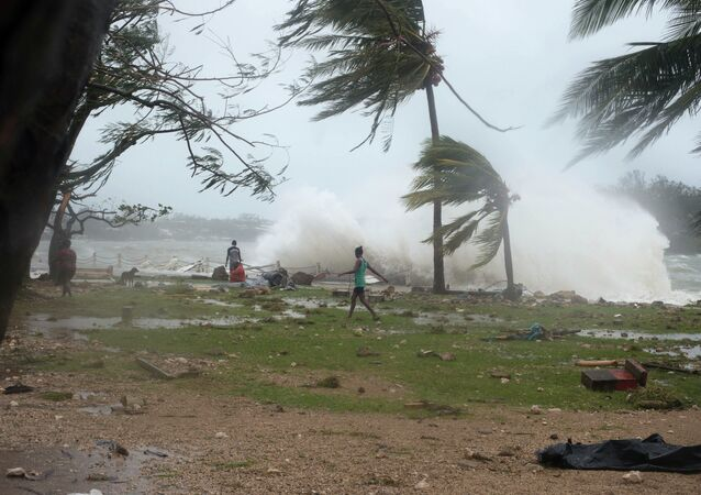 In this image provided by UNICEF Pacific people walk along the shore where debris is scattered in Port Vila, Vanuatu, Saturday, March 14, 2015, in the aftermath of Cyclone Pam