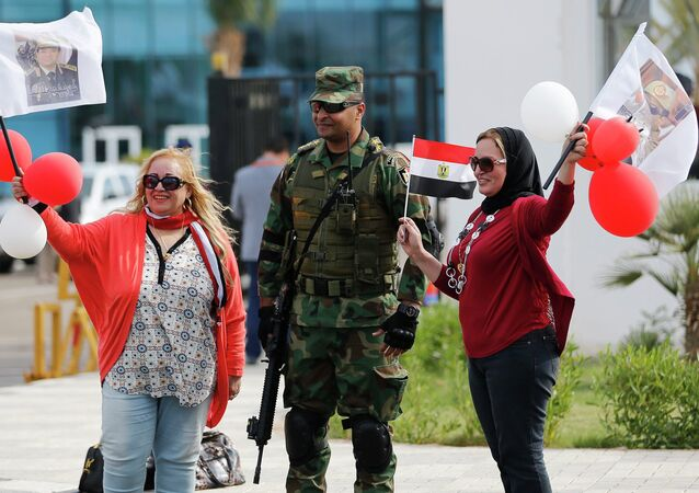 Egyptian women wave flags with pictures of Egyptian President Abdel Fattah al-Sisi, next to a soldier outside a conference centre hosting the Egypt Economic Development Conference (EEDC) in Sharm el-Sheikh, in the South Sinai governorate, south of Cairo, March 14, 2015