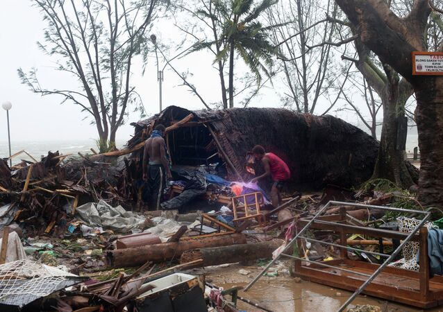 In this image provided by UNICEF Pacific people scour through debris damaged and flung around in Port Vila, Vanuatu, Saturday, March 14, 2015