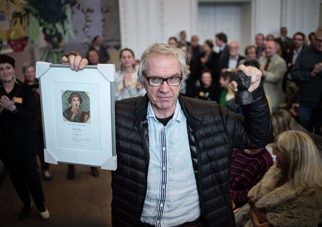 Swedish artist Lars Vilks holds up his Sappho Award plaque after being awarded by Denmark's Free Press Society in Copenhagen March 14, 2015