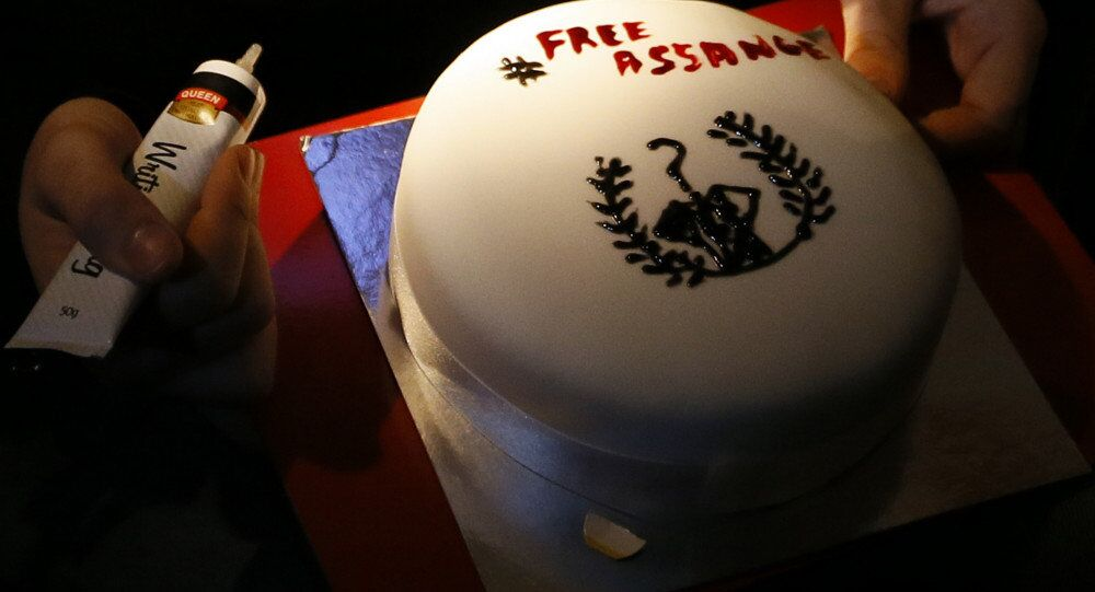A supporter decorates a cake as he waits for Julian Assange, founder of WikiLeaks to speak to the media and members of the public from a balcony at the Ecuadorian Embassy in London.