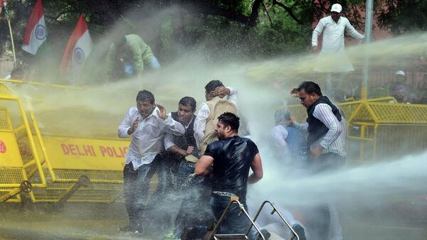 Indian police use water cannons to disperse activists of opposition Congress party's youth wing after they jumped police barricades during a protest against the government's land acquisition bill, in New Delhi, India - Sputnik International