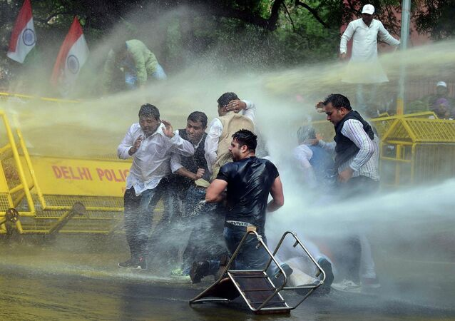 Indian police use water cannons to disperse activists of opposition Congress party's youth wing after they jumped police barricades during a protest against the government's land acquisition bill, in New Delhi, India