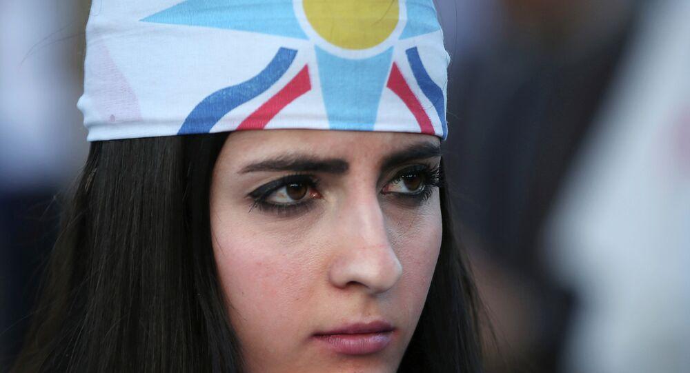 An Assyrian woman wears her community's flag