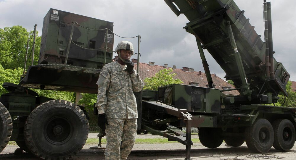 A U.S. soldier stands next to a Patriot surface-to-air missile battery at an army base in Morag, Poland