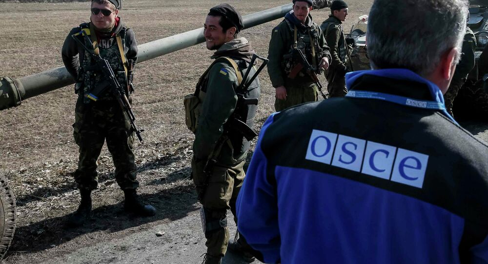 A member of Special Monitoring Mission of the Organization for Security and Cooperation (OSCE) to Ukraine walks along a convoy of Ukrainian armed forces in Blagodatne, eastern Ukraine