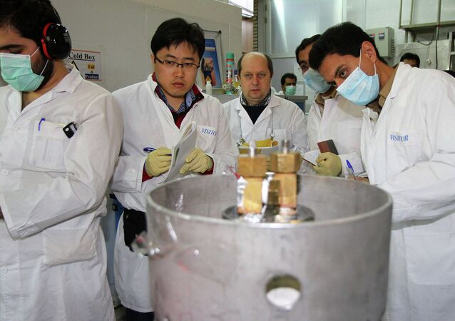 Unidentified International Atomic Energy Agency (IAEA) inspectors (2nd-3rd L) and Iranian technicians disconnect the connections between the twin cascades for 20 percent uranium production at nuclear power plant of Natanz, some 300 kilometres south of Tehran. File photo