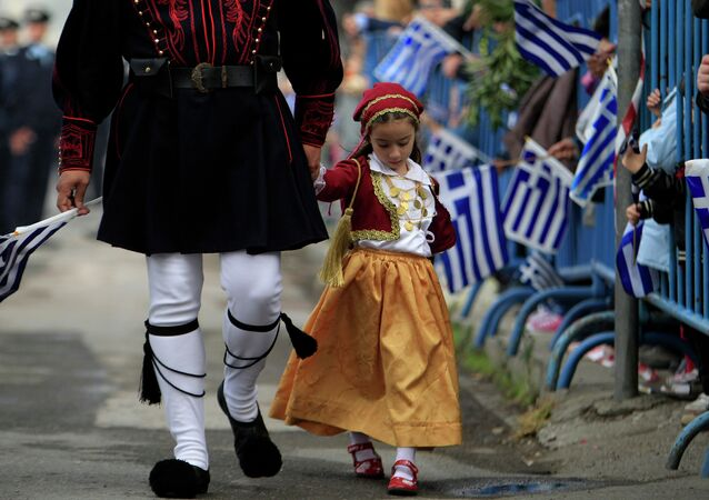 A girl dressed in a traditional costume holds the hand of a man in traditional military uniform during a parade, in the northern port city of Thessaloniki