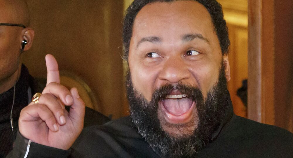 French comedian Dieudonne M'Bala M'Bala gestures to the media as he leaves a Paris court house, Wednesday, Feb. 4, 2015. Controversial French comic Dieudonne has gone on trial charged with defending terrorism in a Facebook post made after the three-day terror spree in Paris last month.