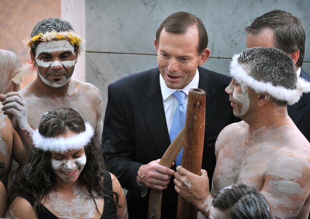 Australian Prime Minister Tony Abbott holding his fighting boomerang while talking to an Aboriginal performer at the opening of the 44th Parliament in Canberra