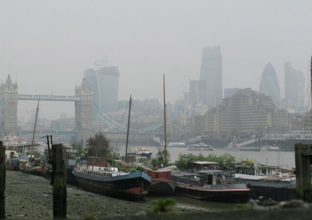 Tower Bridge and the high rise towers of the City of London are shrouded in smog