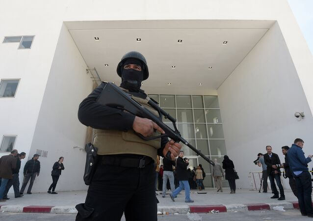 A member of the Tunisian security forces stands guard as journalists gather at the visitors entrance of the National Bardo Museum in Tunis