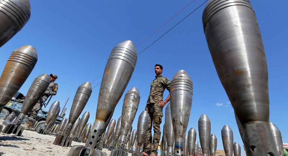 A member of the Iraqi security forces stands between Islamic State ammunition being displayed in al-Alam Salahuddin province March 17, 2015