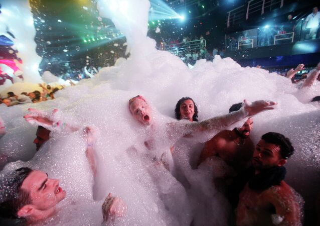 Partygoers dance in foam at The City nightclub in the Caribbean resort city of Cancun, Mexico, early Monday, March 16, 2015