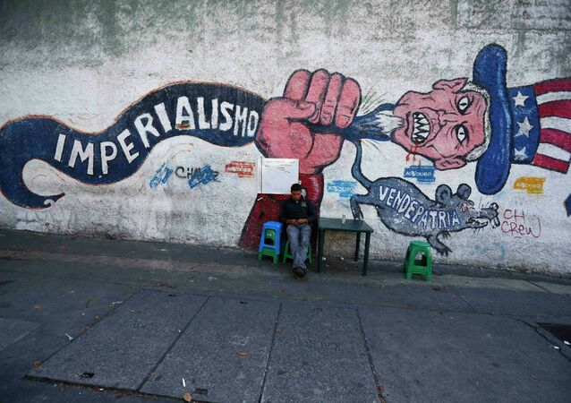 A man sits next to graffti, which reads imperialism and traitor, in Caracas March 9, 2015