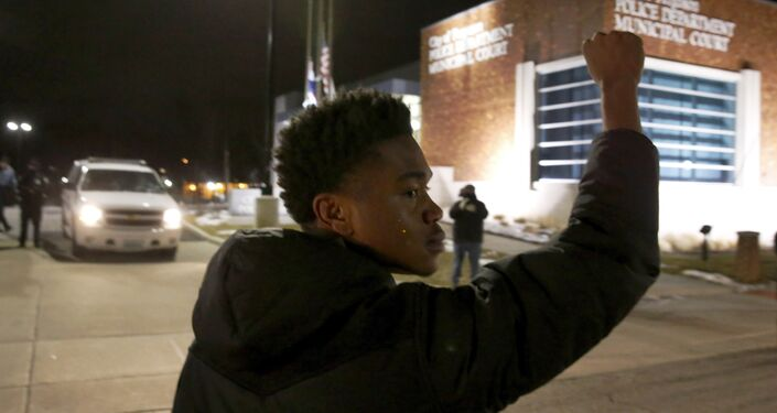 Clifton Kinnie joins protesters as they block traffic on the street outside the Ferguson, Mo.