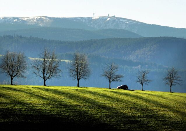 A car drives through the Black Forest near St Maergen backdropped by the Feldberg mountain, southern Germany