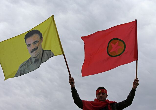 A Kurdish man waves a flag of the Kurdistan Workers' Party, known as PKK, right, and a flag with a portrait of the jailed Turkish Kurdish guerrilla leader Abdullah Ocalan, left, during a demonstration demanding his release, in Beirut, Lebanon