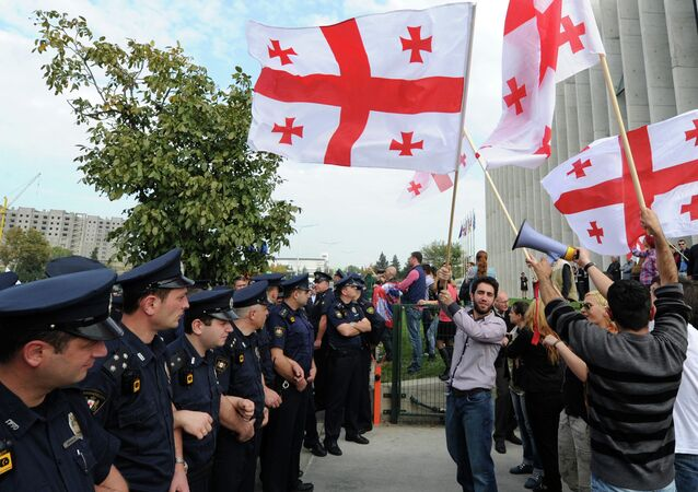 Supporters of the opposition party of former Georgian President Mikhail Saakashvili United National Movement wave flags of Georgia during a protest outside the party's headquarters in Tbilisi on October 15, 2014