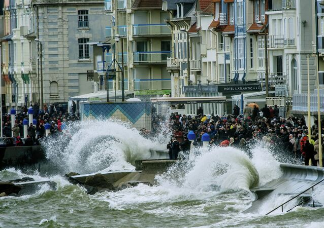 People gather to watch waves breaking on the dyke on March 21, 2015 in Wimereux, northern France