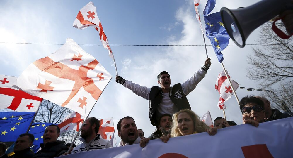 Opposition supporters march on the street during a rally organised by the United National Movement, calling for the resignation of the government in Tbilisi
