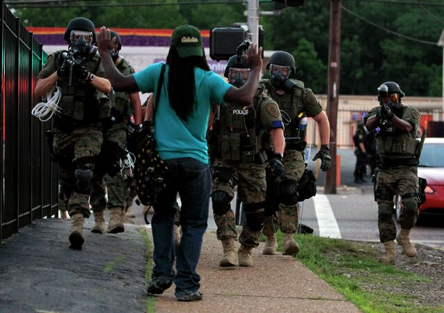 In this Aug. 11, 2014, file photo, police wearing riot gear walk toward a man with his hands raised Monday, Aug. 11, 2014, in Ferguson