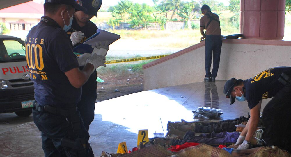 This photo taken on March 8, 2015 shows police investigators looking at dead bodies of alleged Bangsamoro Islamic Freedom Fighters (BIFF)
